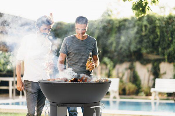 Men enjoying beer and chatting in backyard